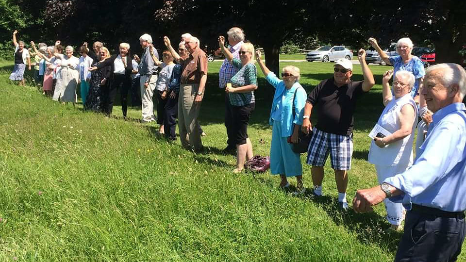 Members of the Greenwood United Church congregation ready to launch wildflower seed.